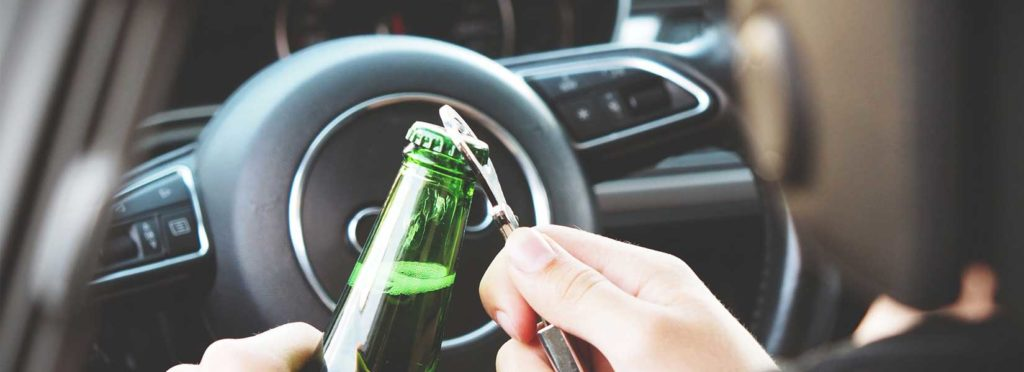 Image showing a person opening a beer while driving