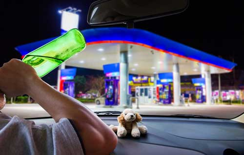 A man drink and driving as he pulls into a gas station.