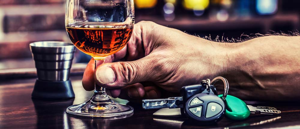 A man holding a glass of alcohol at a bar. The liquor is lying next to a set of keys.