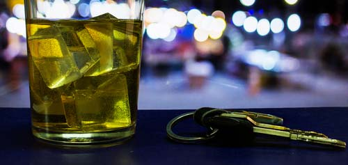 A glass of alcohol on top of the dashboard of a car.